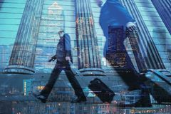 Multiple exposure of city commuters and skyscrapers in London. Multiple exposure of city commuters walking with trolleys and city skyscrapers of the financial Royalty Free Stock Photography