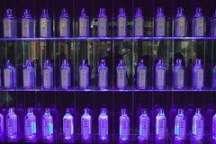 Multiple Gin bottles in purple light decorate shelves in bar in Barcelona, Spain Stock Photography