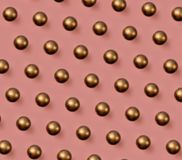 Golden Christmas balls pattern on pink background royalty free stock images