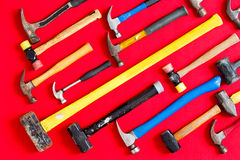 Multiple hammers on a vivid red background. Multiple different mallets and hammers arranged in diagonal lines on a vivid red background in a diversity, DIY Royalty Free Stock Photos