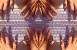 Multiple hands typing on laptop. Hands type on a laptop keyboard turned into an interesting mirrored pattern royalty free stock images