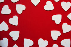 Multiple hearts whites shapes, forming a circular frame, red bac Royalty Free Stock Photography