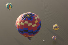 Multiple hot air balloons over water. Aerial view of multiple hot air balloons flying over water Stock Photography