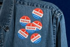 Blue denim working clothing with many Voted stickers on dark background stock image