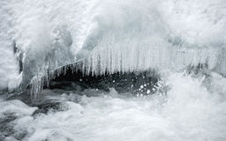 Multiple icicles on mountain river, in hard winter Royalty Free Stock Photo