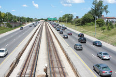 Multiple lane highway with rail tracks. In the middle Royalty Free Stock Image