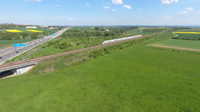Multiple lane highway and railroad track. Aerial view of a multiple lane highway and railroad track, passing highspeed train - panning shot stock video footage