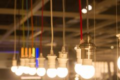 Multiple LED lamps SUN lights and hang in a row on the long cords of different colors. Simple light bulbs technology background, conceptual royalty free stock images