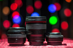 Multiple lenses placed on a table on a background of the blur circle of garland. In the New Year and Christmas stock photos