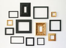Multiple many blank small picture frames on white wall. Background stock photo