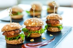 Multiple min beef hamburgers. Close up of mini hamburgers at catering event royalty free stock photos