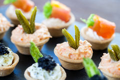 Multiple mini pastry tartlets with seafood filling. Royalty Free Stock Photos
