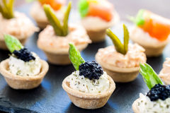 Multiple mini puff pastry tartlets with savory filling. Stock Photos