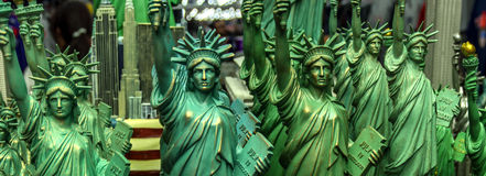 Multiple miniature copies of the statue of liberty in a shop window. Panoramic photo of multiple copies of the statue of liberty in a show window in NYC Stock Image