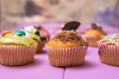 Multiple muffins decorated with multicolored frosting, cocoa powder and beans, candies and whipped cream side view toned selective Stock Photo