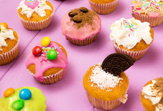 Multiple muffins decorated with multicolored frosting, cocoa powder and beans, candies and whipped cream top view toned selective Stock Photo