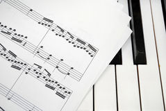 Multiple music score sheets on piano keyboard Royalty Free Stock Photo