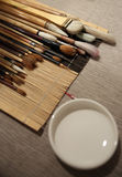 Multiple paintbrushes with a cup besides Royalty Free Stock Photos