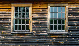 2 multiple paned windows in a weathered and charred wooden wall. Of a colonial barn Royalty Free Stock Photography