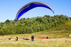 Paragliders are preparing to fly against the backdrop of the beautiful scenery Stock Images