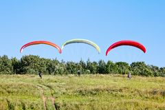 Paragliders are preparing to fly against the backdrop of the beautiful scenery Royalty Free Stock Images