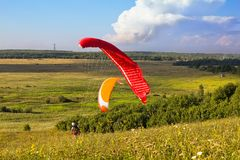 Paragliders are preparing to fly against the backdrop of the beautiful scenery Stock Photos