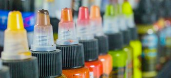 Multiple bottles with colorful inks for tattoo. Multiple plastic bottles with colorful inks for tattoo. Side view. Macro Royalty Free Stock Images
