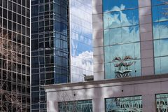 Multiple reflections sky clouds towers building in glass panels Regina Canada. Reflection highrise skyskraper sky clouds patterns textures lines shapes stock image