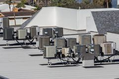 Multiple Rooftop Air Conditioning Units. Multiple air conditioning and heat pump units on top of a large hotel in Florida to handle the hot and humid climate royalty free stock photos