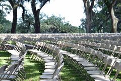 Multiple rows of empty white chairs stock photography