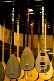 Multiple saz, Turkish long neck lute of different types hanging from the ceiling of a musical shop. stock photos