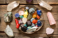 Multiple semi precious gemstones on board. Multiple semi precious gemstones on wooden board fluorite, quartz, smoky quartz, rose quartz and others royalty free stock photography
