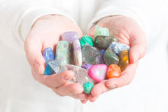 Multiple semi precious gemstones. In hands royalty free stock photos