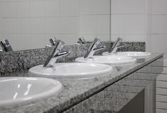 Multiple sinks and taps at public toilet Royalty Free Stock Photos