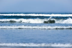 Multiple small waves break near shore Stock Photography
