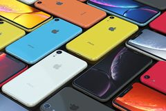 Arrangement of iPhone XR all colours, landscape. Multiple smartphones - iPhone XR Silver, Space Gray, Red, Blue, Yellow and Coral, arranged in a mosaic pattern stock photography
