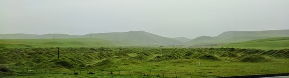 Panorama fantasy green vista rolling hills on misty day stock photography
