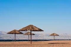 Multiple sunshades on a beach. Sunshades near on beach of the Read Sea in Aqaba, Jordan. City of Eilat, Egypt in background royalty free stock photo