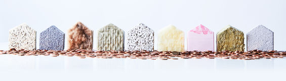 Multiple textured house shapes on white background. Nine textured house shapes surrounded by coins on an isolated white background representing an affluent stock images