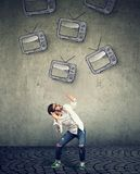 Multiple TV sets falling on a strssed scared man. Multiple TV sets falling on a strssed scared young man stock photography