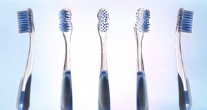 Multiple views of transparent blue toothbrush. On pink and blue gradient background. Horizontal composition stock image
