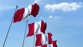 Multiple waving flags of Peru against the blue sky