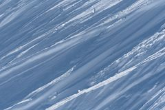 Multiple wind packed snow ridges forming oblique lines in sunshi. Landscape format view of ridges forming oblique lines in wind packed snow Stock Photos