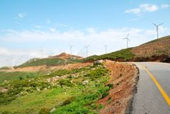 Multiple wind turbine power plants and a road Royalty Free Stock Photos