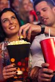 Multiplex movie theater. Young couple in multiplex movie theater, eating popcorn. Focus on hands and popcorn Royalty Free Stock Photos