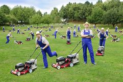 Multiplied several times man with lawn mower. Many gardeners with lawn mowers mow a large garden plot Stock Image