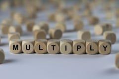 Multipliez - le cube avec des lettres, signe avec les cubes en bois photographie stock libre de droits