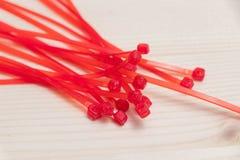 Multiplo legame rosso di molti legami dello zip isolato su legno fotografia stock libera da diritti