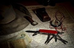 Multipurpose knife, compass, money and hat on an old map royalty free stock photography