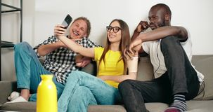 Taking a Selfie. Multirace friends having fun taking selfie on smartphone on comfortable grey sofa, youth lifestyle concept stock video